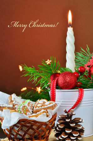 Christmas background, greeting card with burning candle, decorations, gingerbread cookies and fir branches  in basket Standard-Bild - 91097360