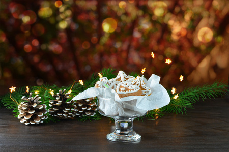 Christmas background, greeting card with lights, gingerbread cookies, fir cones and branches on wooden table Standard-Bild - 91130038