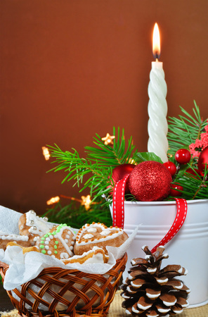 Christmas background, greeting card with burning candle, decorations, gingerbread cookies and fir branches  in basket Standard-Bild - 91290174