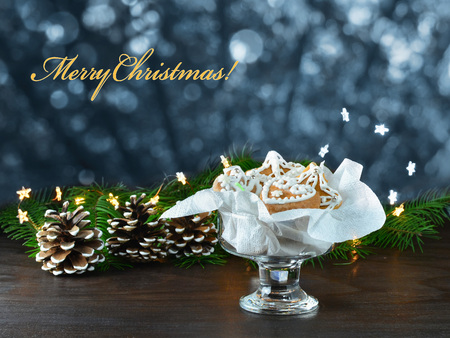 Christmas background, greeting card with lights, gingerbread cookies, fir cones and branches on wooden table Standard-Bild - 91172266
