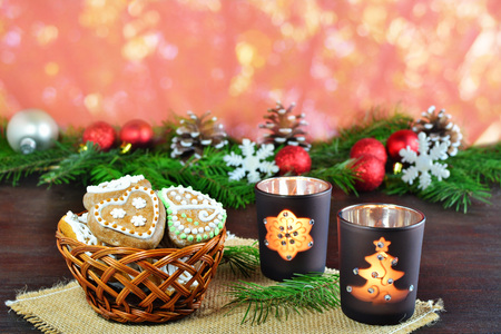 Christmas background, greeting card with burning candles, decorations, gingerbread cookies and fir branches  in basket over vibrant bokeh background Standard-Bild - 91344950