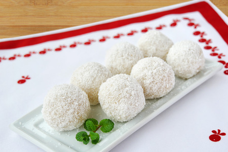 Coconut white chocolate balls on white serving plate. Fancy confection truffles covered with desiccated coconut on the table