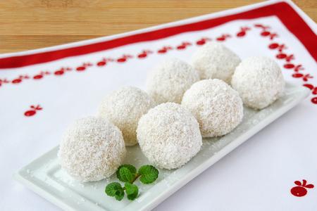 Weiße Schokoladenkugeln der Kokosnuss auf weißer Umhüllungsplatte. Fantastische Konfekttrüffel bedeckt mit ausgetrockneter Kokosnuss auf dem Tisch Standard-Bild - 92208563