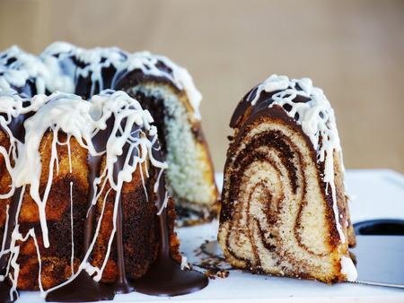 Marble bundt cake with dark and white chocolate icing sliced. Slice of marbled ring cake over cake server. Standard-Bild - 92196846