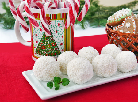Christmas goodies on the table, coconut candies on white serving plate, candycanes and gingerbread cookies in basket Standard-Bild - 92249280