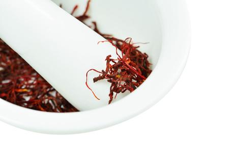 Dried saffron threads in white ceramic mortar isolated on white (Crocus sativus) Standard-Bild - 92834708