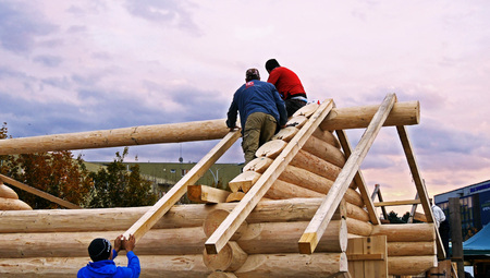 CLUJ-NAPOCA, ROMANIA - OCTOBER 13, 2017: Log cabin building. Carpenters lift square timber rafters to the roof, building frame structure for log cabin at sunset Standard-Bild - 93040385