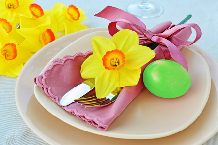 Simple table setting arrangement with cream porcelain dishes, green Easter egg, yellow daffodil flower, cutlery and napkin Standard-Bild - 93770468