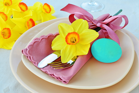Simple table setting arrangement with cream porcelain dishes, pastel blue Easter egg, yellow daffodil flower, cutlery and napkin