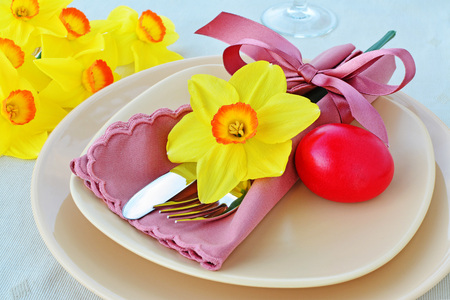 Simple table setting arrangement with cream porcelain dishes, red Easter egg, yellow daffodil flower, cutlery and napkin