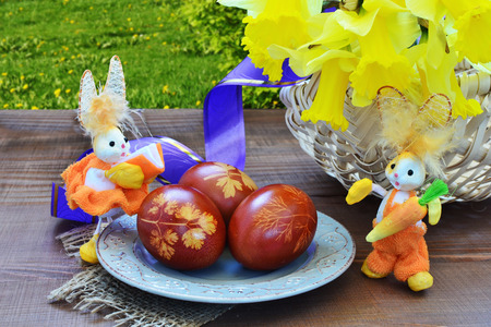 Eater scene with Easter eggs, daffodil flowers in basket and toy bunnies