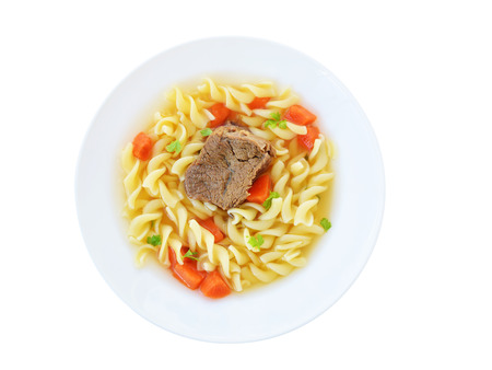 Bouillon clear beef broth with noodles and vegetables in white plate isolated, top view