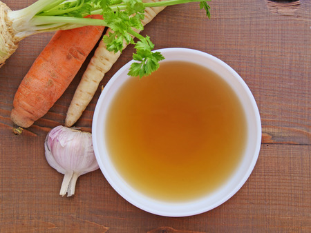 Clear beef broth, bone broth, bouillon in white bowl and vegetables on wooden table top view Standard-Bild - 99472930