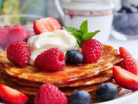 Keto pancake a base di farina di cocco o farina di mandorle, serviti con frutti di bosco e panna montata Archivio Fotografico