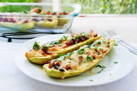 White zucchini boats stuffed with sausage and pizza filling and grated mozzarella cheese