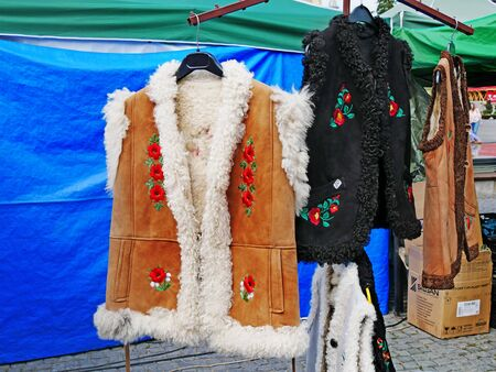 Hand embroidered Romanian traditional sheepskin vests and waistcoats hanged at the market in Cluj-Napoca, Romania on circa September, 2017