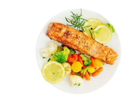 Grilled salmon fillet with vegetables, lemon and rosemary over white plate isolated, top view, overhead. 写真素材