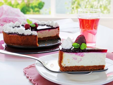 No-bake cheesecake slice on cake cutter over white plate. Easy cheesecake with graham cracker crust, cream cheese filling and raspberry jelly, decorated with whipped cream. glass of refreshing pink dr