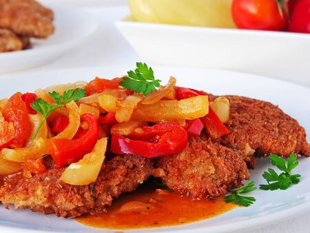 Homemade breaded schnitzel served with lecho. Crispy breadcrumb coated fried meat served with vegetable stew.