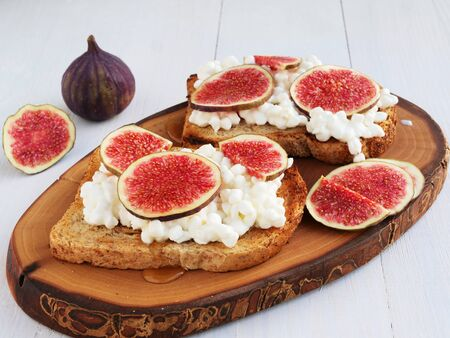 Toast with cottage cheese, figs and honey, two slices served on a wooden board. 写真素材