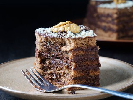 Layered chocolate cake squares with chocolate cream filling and walnut on plate. A piece already eaten. Stock fotó