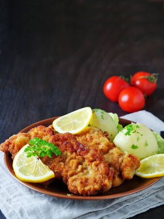Wiener Schnitzel with potato salad served with lemon slices and parsley leaves