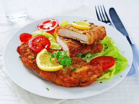 Wiener schnitzel over lettuce leaves with sliced tomatoes and lemon on white plate.