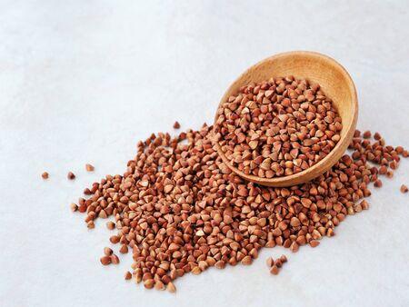 Dry buckwheat grains in wooden bowl (Fagopyrum esculentum) Stock Photo