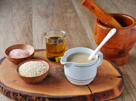 Tahini sauce in pitcher  with ingredients. Sesame seeds, olive oil and salt on wooden board. Фото со стока