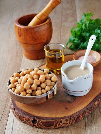 Hummus ingredients, chickpeas, tahini sauce, salt and olive oil  on wooden board, vertical