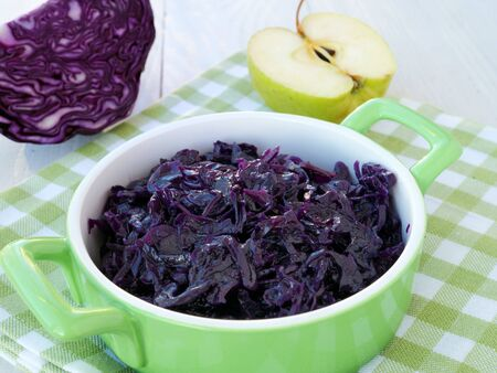 Braised red cabbage with apples in green ceramic dish. Side dish served with venison, goose, pork or chicken roast.