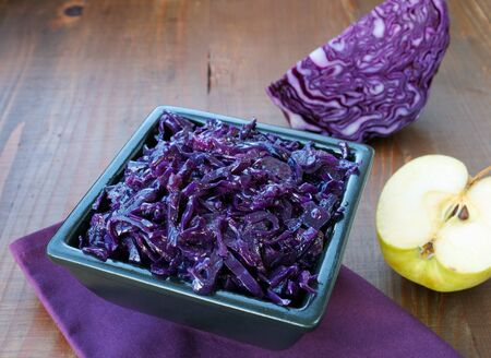 Sauteed red cabbage with apples in black square  bowl. Traditional side dish to be served with venison, goose, pork or chicken roast. Фото со стока