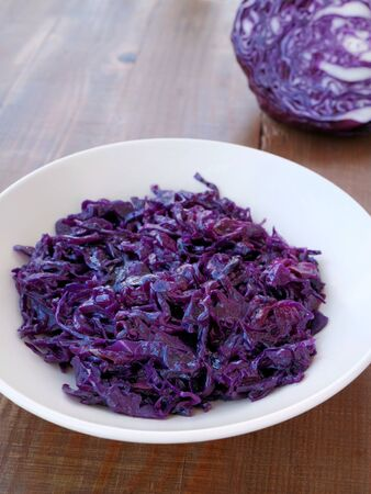 Traditional braised red cabbage in bowl. Side dish served with venison, goose, pork or chicken roast. Фото со стока