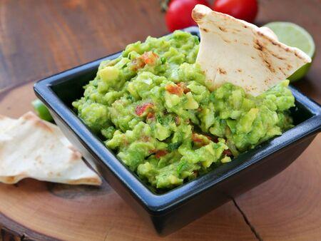 Avocado dip in black square bowl on wooden chopping board.Mexican guacamole spread. Фото со стока