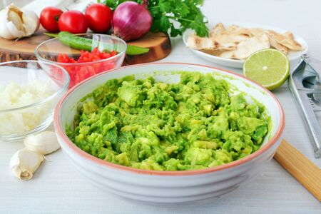 Mashed avocado along with diced onions and tomatoes  in bowls for making avocado dip. Preparing ingredients for guacamole with ingredients and kitchen utensils on table