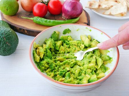 Chef hand mashes avocado with the back of a fork in a mixing bowl. Making guacamole dip with ingredients on table.