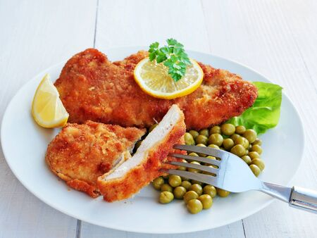 Bite of breaded chicken breast on fork. Meal of crispy chicken cutlets with green peas served with lemon slices and lettuce.