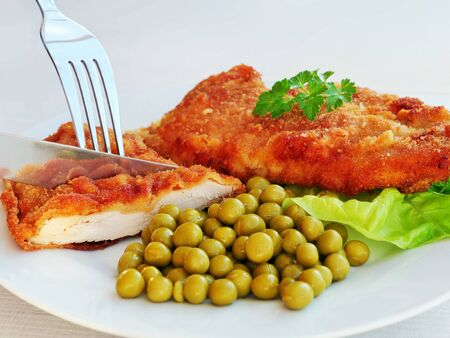 Cutting a piece of crispy breaded chicken cutlet with a fork and knife. Dinner plate with  breaded chicken breast and green peas over lettuce leaves.