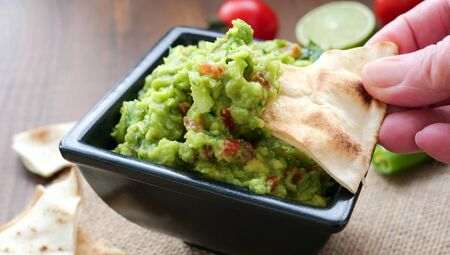 Hand dipping wheat tortilla chips into a bowl of freshly made guacamole