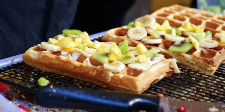 Delicious waffles topped with fresh fruits are being prepared at a food booth Фото со стока