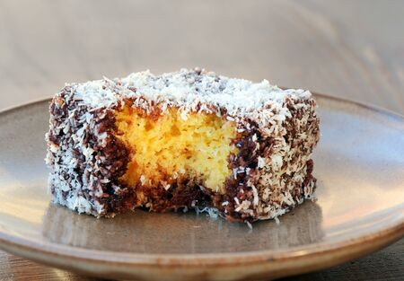 Lamington cake closeup with a bite missing. Squares of sponge cake coated in chocolate sauce and rolled in desiccated coconut