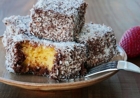 Lamington cake, squares of sponge cake coated in chocolate sauce and rolled in desiccated coconut on plate