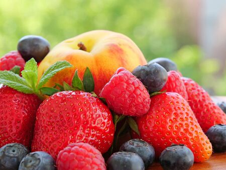 Pile of ripe summer fruits and berries over an outdoor table Фото со стока