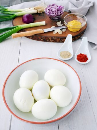 Making egg salad with hard-boiled eggs, spices and ingredients, vertical Фото со стока