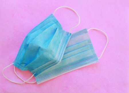 Disposable medical 3ply face mask with earloops on pink background
