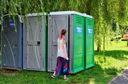 Blurred young woman is entering a portable toilet. Ecological WC units placed in the shadow of willow trees in Cluj-Napoca, Romania on August 14, 2016