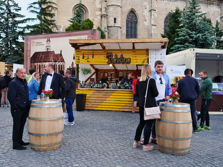 People have drinks at barrel tables in front of several food and wine booths in Cluj-Napoca, Romania on May 19, 2018 Редакционное