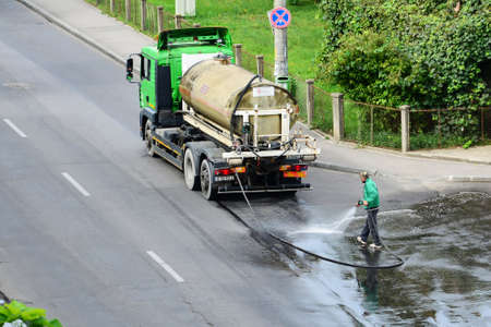 Utility worker washes and disinfects the asphalt on the street with a hose connected to a cistern truck in cluj-Napoca, Romania on August 26, 2014