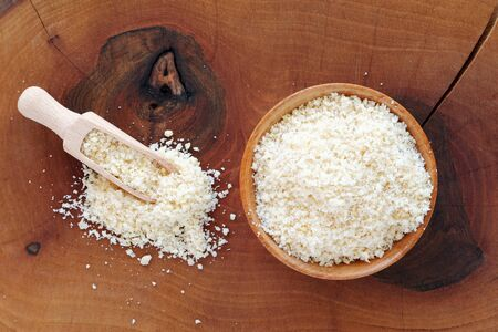 Almond flour in wooden bowl and scoop over wooden board top view Фото со стока