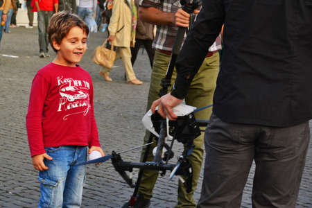 Happy young boy looks with admiration at a drone in the hand of a drone pilot in Cluj-Napoca, on October 4, 2015